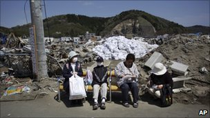 A family sit on seats in rubble in Ishinomaki on 5 May 2011