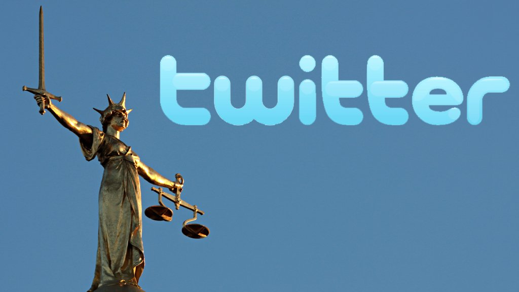 Twitter logo next to Justice statue
