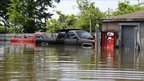 Two pickup trucks are seen surrounded by floodwater outside a garage in Memphis, Tennessee, 8 May 2011