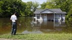 A man stands in front of a partially submerged house in Memphis, Tennessee, 8 May 2011.