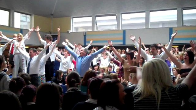 The head of a high school, along with some of his teachers, surprise pupils with an impromptu dance performance in the school canteen