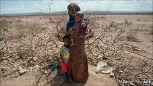 Woman stands with her two children in a landscape left dry and barren by drought