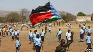 A Sudanese man waves the regional flag of southern Sudan during a protest in Kauda on 15 January 2011 calling for electoral reforms in the Nuba Mountains