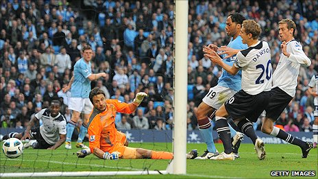 Tottenham striker Peter Crouch (right) diverts the ball into his own net from a James Milner cross to give Man City the lead