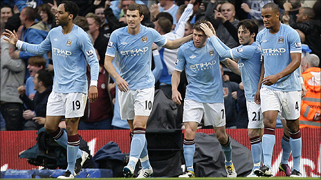 Man City's James Milner (centre) is congratulated by team-mates after his cross was turned into his own net by Tottenham striker Peter Crouch