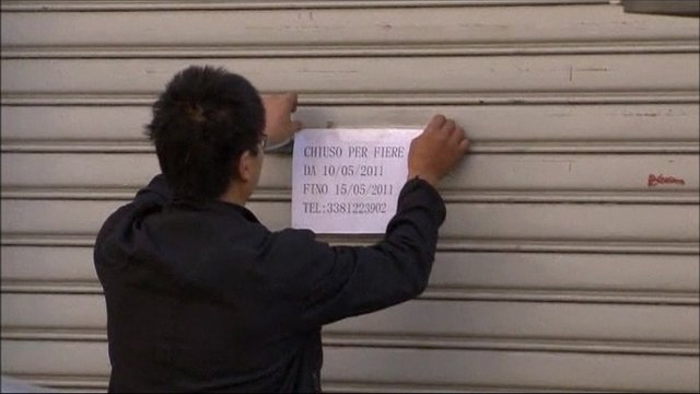 Man sticking up sign saying his shops is closed
