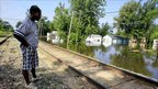 Man looking out over a railway track at flood waters