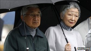 Japan's Emperor Akihito (L) and Empress Michiko visit at an area devastated by the 11 March tsunami in Fukushima prefecture