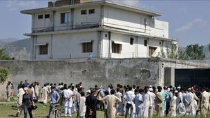 Pakistani media personnel and local residents gather outside the hideout of Al-Qaeda leader Osama bin Laden following his death by US Special Forces in a ground operation in Abbottabad on May 3, 2011