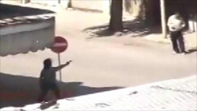 Man shooting a gun on a street in Hama, Syria