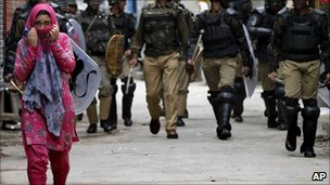 A woman walks ahead of security forces in Srinagar in April 2011