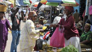 A street market in Libreville. A woman buys fruit from a femail fruitseller.