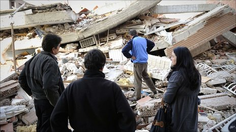 People stand in front of a collapsed building in Lorca