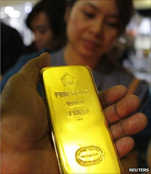 Man holding a gold bar at an Asian trade fair (Image: Reuters)