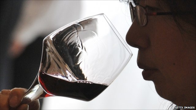 A woman tasting red wine