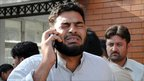 Man talks on phone in Peshawar, near the site of the twin bomb attacks in Shabqadar, Charsadda district, north-west Pakistan - 13 May 2011