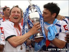 QPR boss Neil Warnock holds the Championship trophy with Alejandro Faurlin, the midfielder whose transfer to the club had been at the centre of the FA hearing
