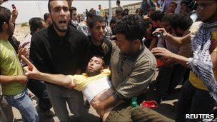 A wounded Palestinian is carried at the Erez border crossing between Gaza and Israel - 15 May 2011