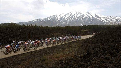 Cyclists pedal as the Etna volcano is seen in background