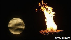 The moon rises over the Olympic torch and flame and the National Stadium during the Beijing 2008 Games