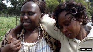 Triza Njeri (R), wife of Olympic marathon champion Samuel Wanjiru, is assisted by an unidentified lady after viewing his body at a funeral home in Nyahururu on Monday