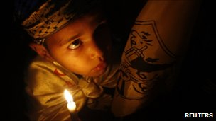 A Palestinian boy holds a candle during a Nakba rally in Khan Younis
