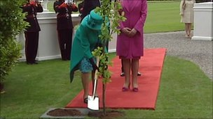 The Queen planting a tree at the Irish presidential palace in Dublin
