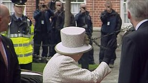 The Queen waves when she arrives at Trinity College