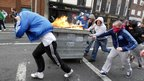 Protesters push a burning rubbish bin towards riot police during a demonstration in north Dublin