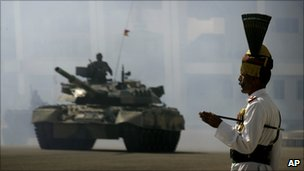A Pakistani officer stands guard as an T-82 tank rolls past during the Pakistan National Day parade in Islamabad, Pakistan