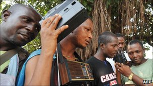 Young Guinean men listening to political news on a radio