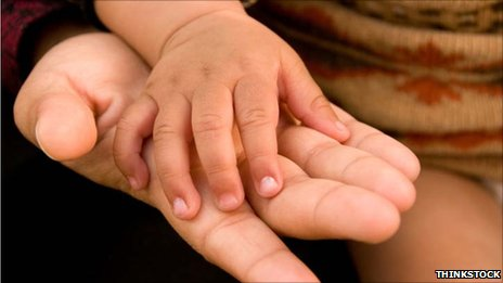 A baby&#039;s hand rests on a woman&#039;s hand