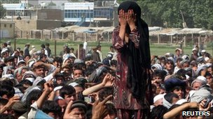 An Afghan girl whose family members were killed in the Nato raid covers her face as she weeps during the Taloqan protest