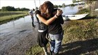 The owner of a local business in Vidalia in Louisiana is hugged by her daughter after floodwaters damaged her property