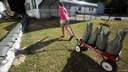A girl in Mississippi helps move sandbags with a toy wagon