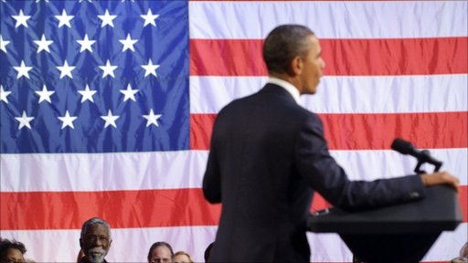 President Obama making a speech in front of the American flag