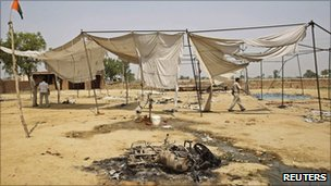 Policeman walks by a burnt motorcycle and tent at Bhatta Parsaul - 8 May 2011