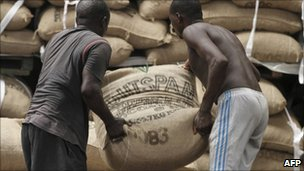 Workers move cocoa sacks at Abidjan's port, 8 May 2011