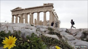Boy runs past the Parthenon in Athens