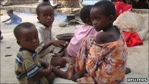 Internally displaced children outside their family's makeshift shelter at a camp in Mogadishu
