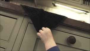 Still from film showing boy pulling tea towel from work surface