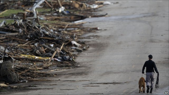 A rescue worker walks past debris at Joplin High School (23 May 2011)