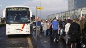 Thomas Cook passengers wait to board buses at Glasgow Airport in Scotland ahead of travelling to Manchester for their onward journey