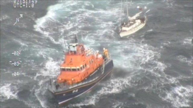 An RNLI vessel tows The Black Swan to safety