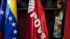 An employee prepares the room with Venezuelan and PDVSA flags ahead of a news conference by Venezuelan officials on 24 May