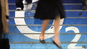 A woman walks over an o2 logo