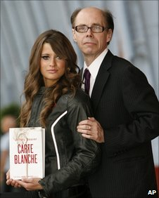 Thriller writer Jeffery Deaver (R) poses for photographers with model Chesca Miles on a BSA Spitfire motor-bike to launch the new James Bond book Carte Blanche