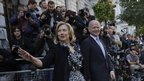 US Secretary of State Hillary Clinton, waves to members of the media as she walks with British Foreign Secretary William Hague,