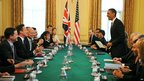 US President Barack Obama takes a seat for an expanded bilateral discussion with the UK's Prime Minister David Cameron (second-left) and other delegations at 10 Downing Street in London