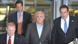 Dominique Strauss-Kahn (centre) being escorted out of the building where he had been staying in lower Manhattan